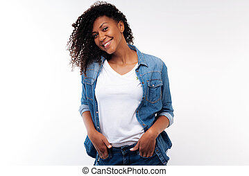 Charming curly woman holding hands in pockets of jeans