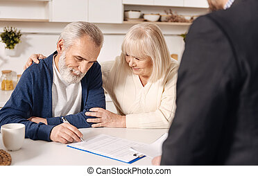 Charming cute elderly couple signing documents at home