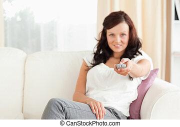 Charming cute woman watching TV