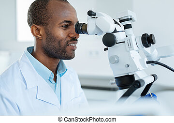 Charming dentist examining mouth cavity with microscope