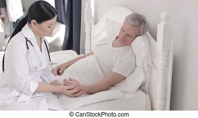 Charming doctor takes care of a disabled senior man in bed