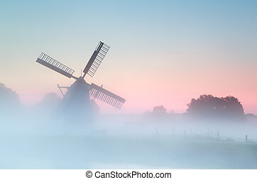 charming Dutch windmill in dense sunrise fog