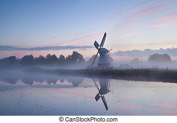 charming Dutch windmill in morning mist at sunrise