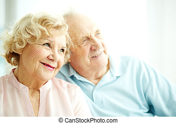 Close-up portrait of a charming elderly woman with her husband on background