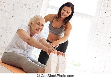 Charming elderly female holding hands on her feet
