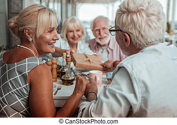 Charming elderly female person looking at her husband