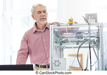 Charming elderly man controlling work of 3D printer
