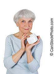 elderly woman applying cosmetic