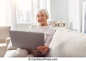 Charming elderly woman reading email on her laptop