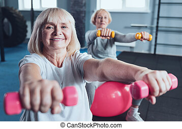 Charming elderly woman smiling for camera while lifting dumbbells