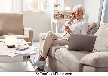 Charming elderly woman talking with her friend on the phone