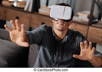 Charming energetic man testing newest VR gear