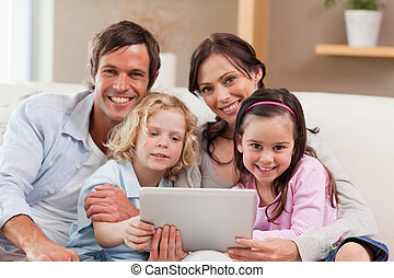 Charming family using a tablet computer in a living room