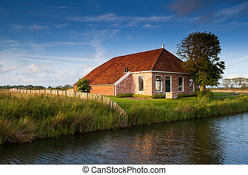 charming farmhouse by river in sunlight