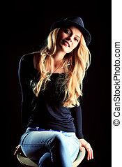 Charming fashion model posing over black background.