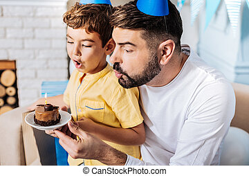 Charming father blowing out candle on cake together with son...