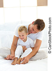 Charming father playing with his boy on a bed