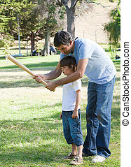 Charming father teaching baseball to his son