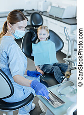 Charming female dentist selecting appropriate instrument