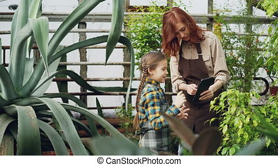 Charming female garderner and her little daughter are using tablet while working in greenhouse together. Modern technology, happy family and gardening concept.