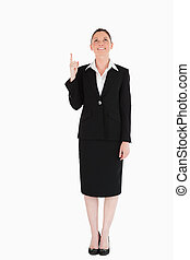 Charming female in suit pointing at a copy space