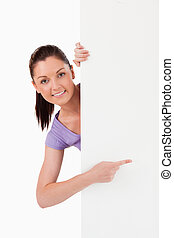 Charming female pointing at a copy space while standing
