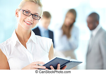 Charming female - Portrait of busy secretary with notepad...