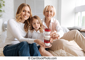 Charming females making a tower with cream jars - Creativity...
