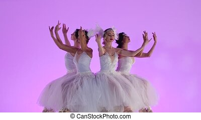 Charming feminine ballerinas dressed as a white swan dance sitting on the top of a cake decorated with flowers. A group of young women gracefully moves in slow motion on a pink background in the studio. Festive theatrical dance show. Close up.