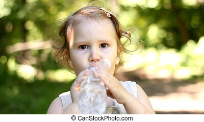 Charming funny happy child is drinking water from a bottle in the summer.