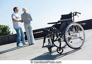 Charming gallant man accompanying elderly lady