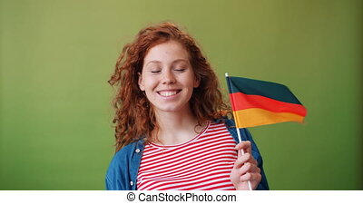 Charming German teenage girl holding national flag of Germany smiling