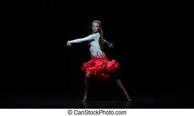 Charming girl dancing elements cha-cha-cha, dark background. Slow motion