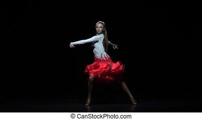 Charming girl dancing elements cha-cha-cha, dark background. Slow motion