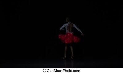 Charming girl dancing elements rumba, dark background. Slow motion