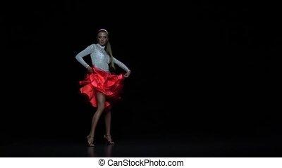 Charming girl dancing elements salsa, dark background. Slow motion