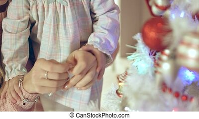 Charming girl hangs a star on the Christmas tree with mother