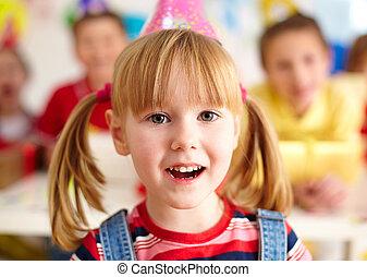 Charming girl - Happy girl in birthday cap looking at camera...