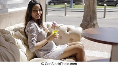 Charming girl having refreshing drink in cafe - Beautiful...