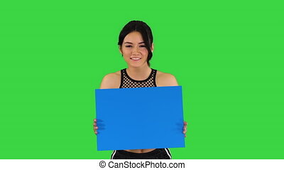 Charming girl holding empty board and dancing on a Green Screen, Blue mockup.