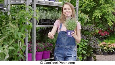 Charming girl holding flowerpot in garden - Beautiful...