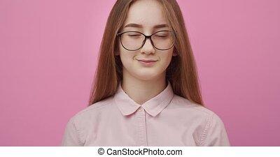Charming girl in eyeglasses smiling over pink background - ...