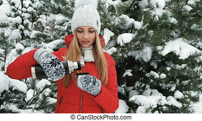 Charming girl in red coat drinking hot tea from thermos....