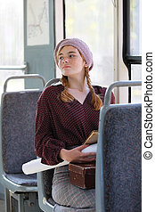 Charming girl in retro style clothes rides in a tram  on a summer day
