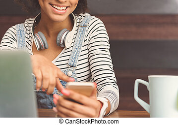 Charming girl is reading news using mobile phone