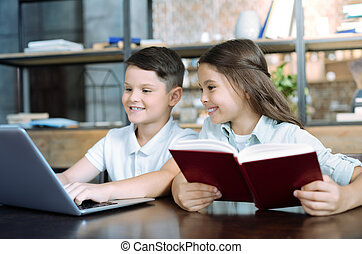 Charming girl looking at brother playing on laptop