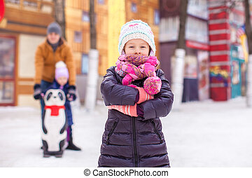 Charming girl on skating rink, dad with little sister in the background