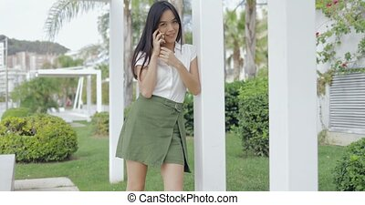Charming girl talking phone outside