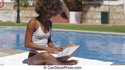 Charming girl with laptop in pool - Beautiful ethnic model...