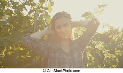 Charming girl with long hair posing next to a vineyard